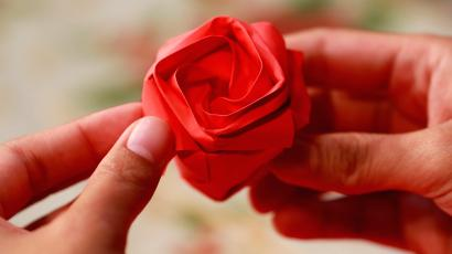 An origami rose between a pair of hands