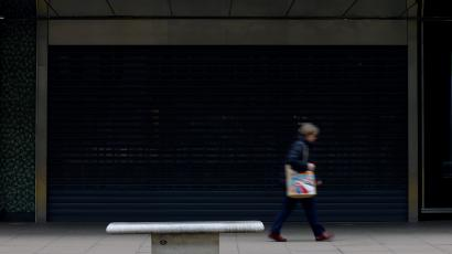 A woman carrying a bag walks past a temporarily closed John Lewis department store on Oxford Street in London
