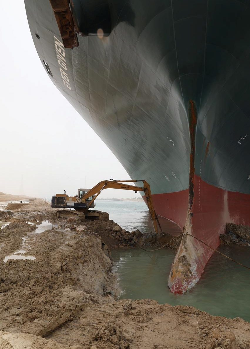 An excavator attempts to free stranded container ship Ever Given, one of the world's largest container ships, after it ran aground, in the Suez Canal.