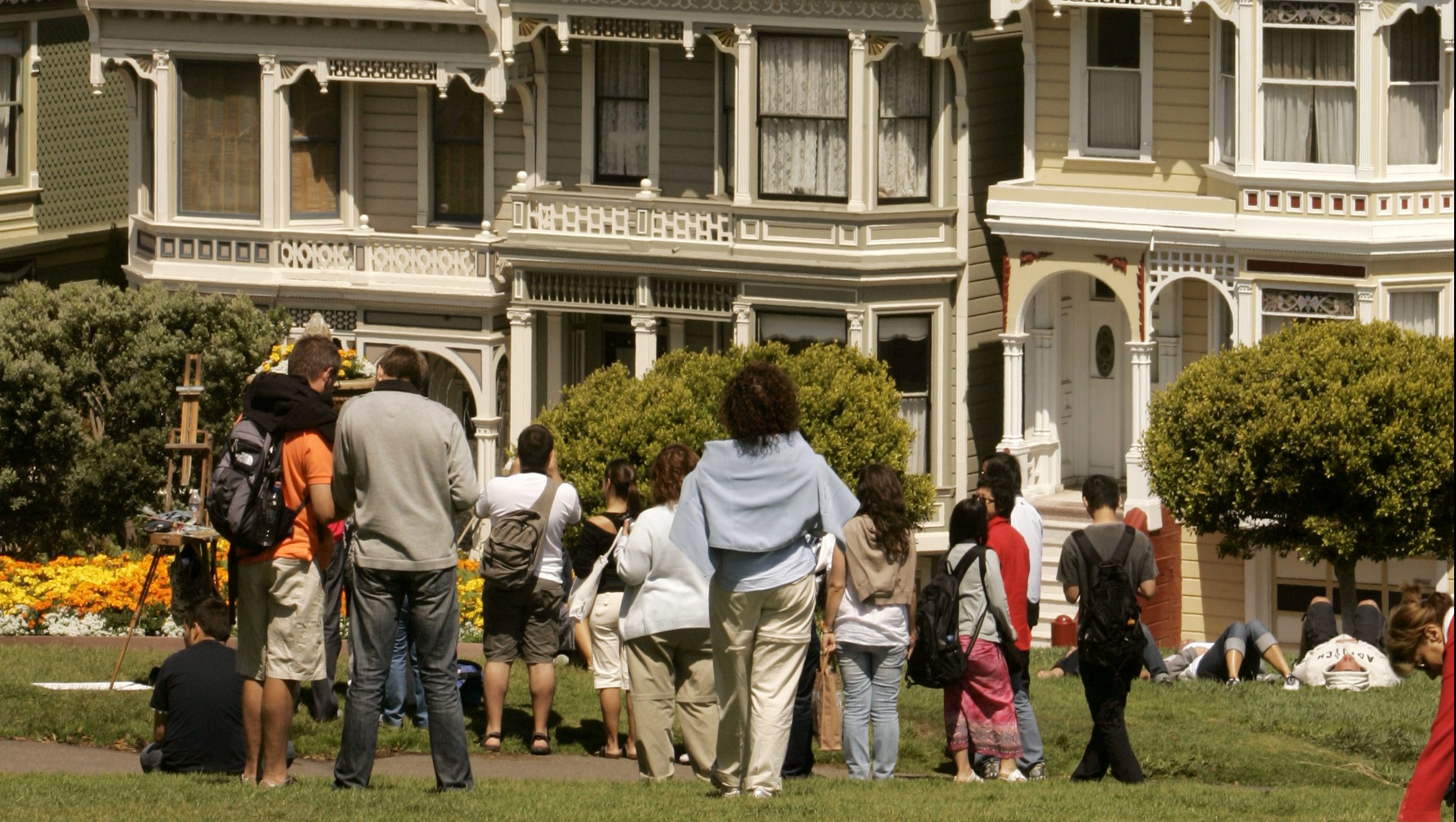 """Visitors look at the skyline of San Francisco, including Victorian homes known as the """"Painted Ladies,"""" in San Francisco, California August 14, 2008."""