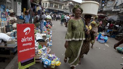 A woman walks past a sign advertising the mobile banking service Airtel Money in Freetown.