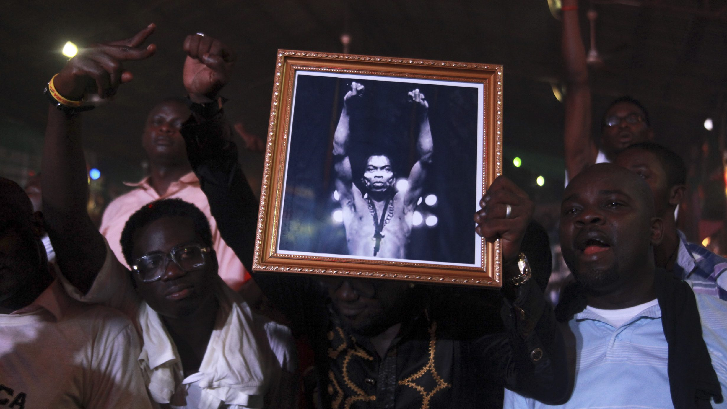 People hold up a photo of Nigeria's music legend Fela Kuti at a night show marking the end of a week-long celebration in his honour, in Lagos October 22, 2012