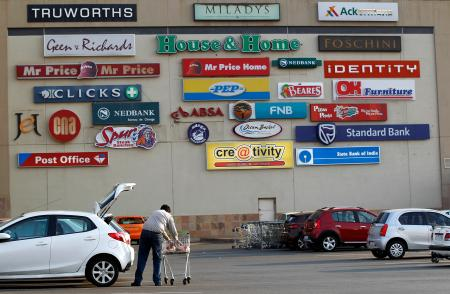 A shopper loads groceries into his car as logos of shops are seen on a wall at a shopping centre in Lenasia, south of Johannesburg.