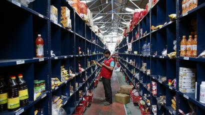 An employee scans a package for an order at a Big Basket warehouse on the outskirts of Mumbai November 4, 2014. Put off by snarled city traffic and a shortage of parking, more Indians are shopping for groceries online, helping e-tailers like Bigbasket.com and Localbanya.com turn in profits while supermarkets are struggling. Picture taken November 4. To match INDIA-INTERNET/RETAIL REUTERS/Danish Siddiqui (INDIA - Tags: BUSINESS FOOD)