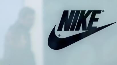 A customer is reflected in a shop window decorated with Nike store logo