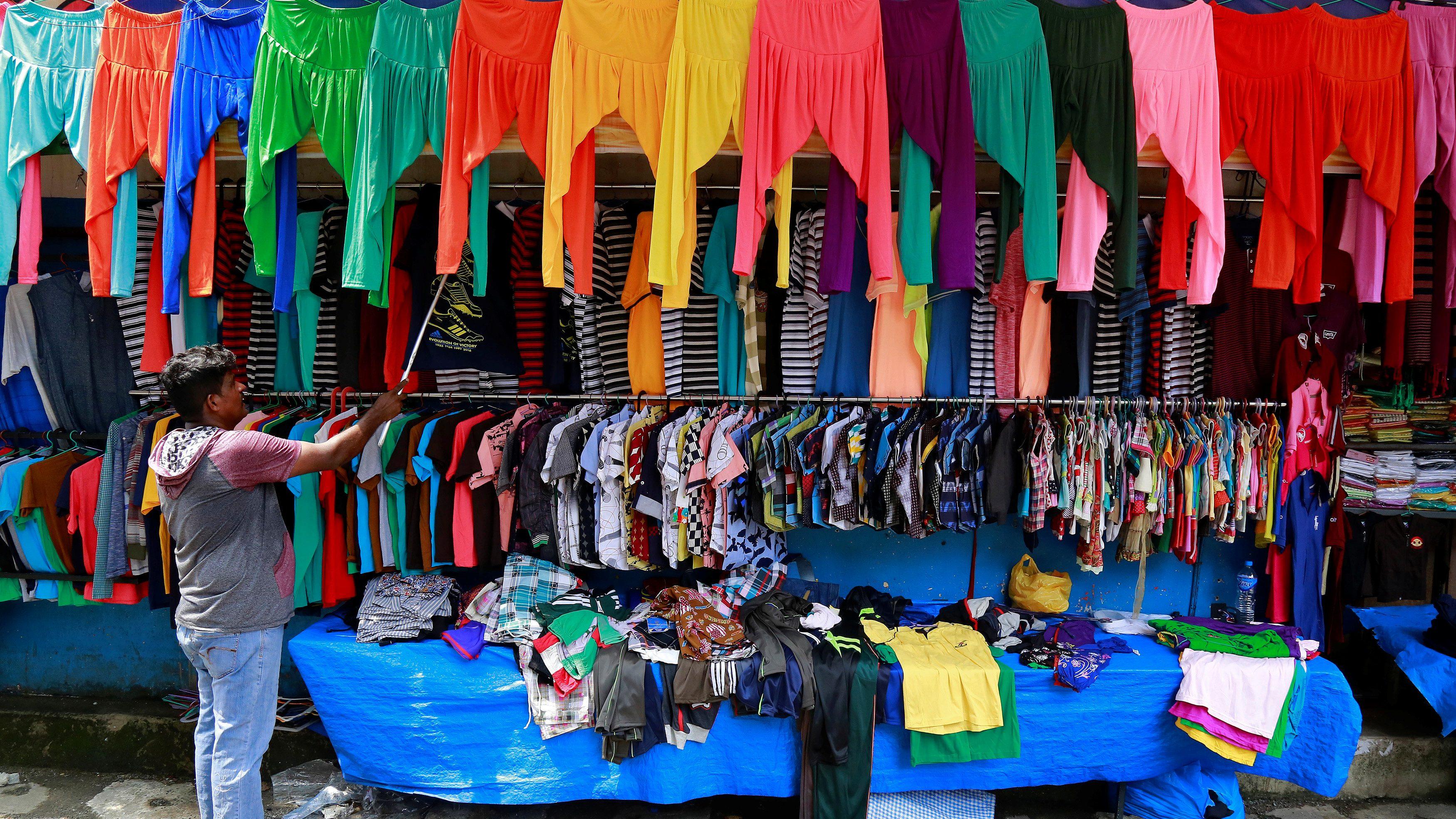 A vendor arranges clothes at his roadside shop in Kochi