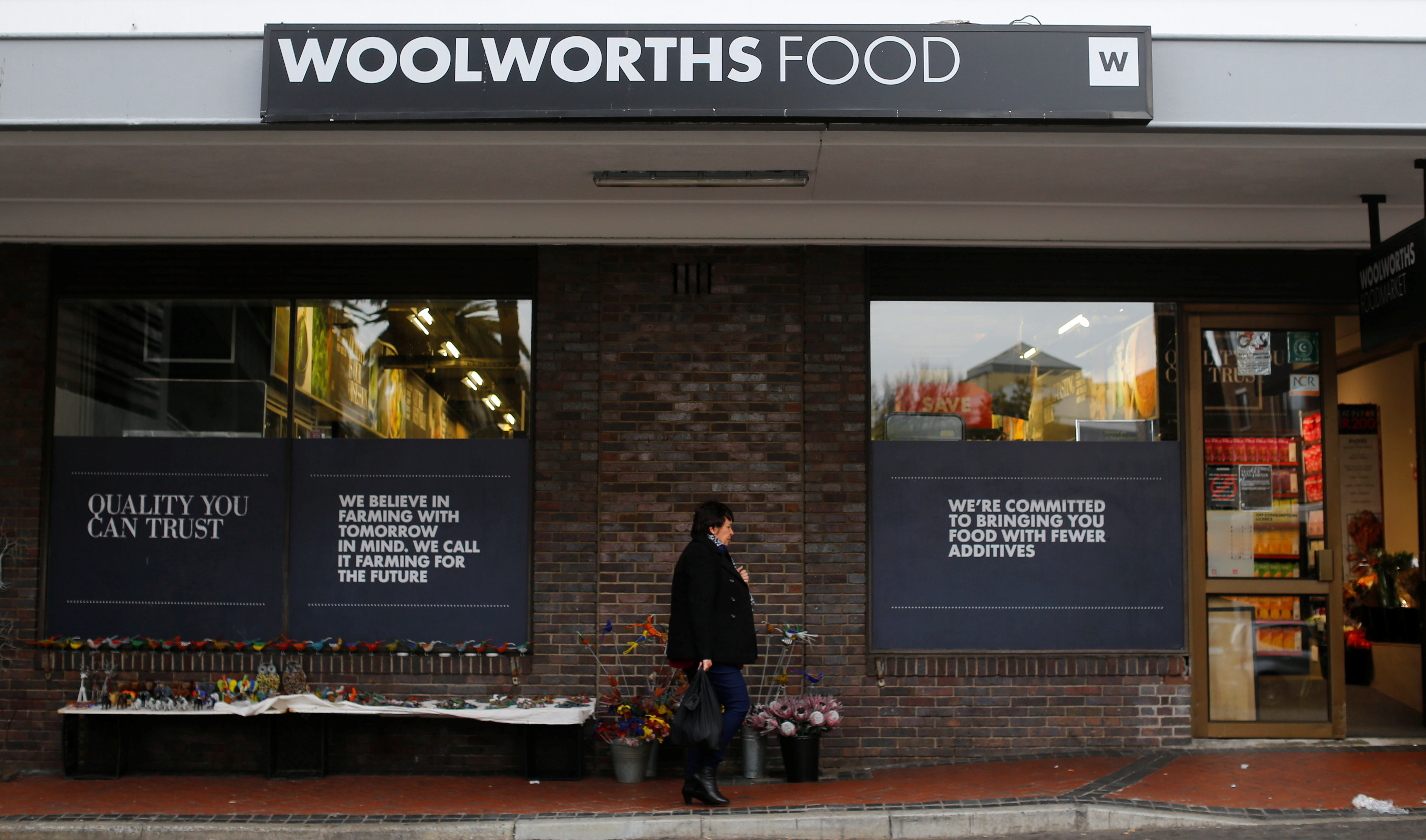 A woman walks past an outlet of retailer Woolworths in Cape Town, South Africa.
