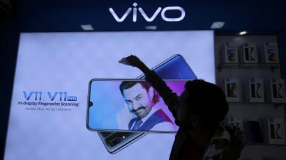 A man cleans a screen displaying a phone model of Chinese smartphone maker Vivo inside a shop in Ahmedabad