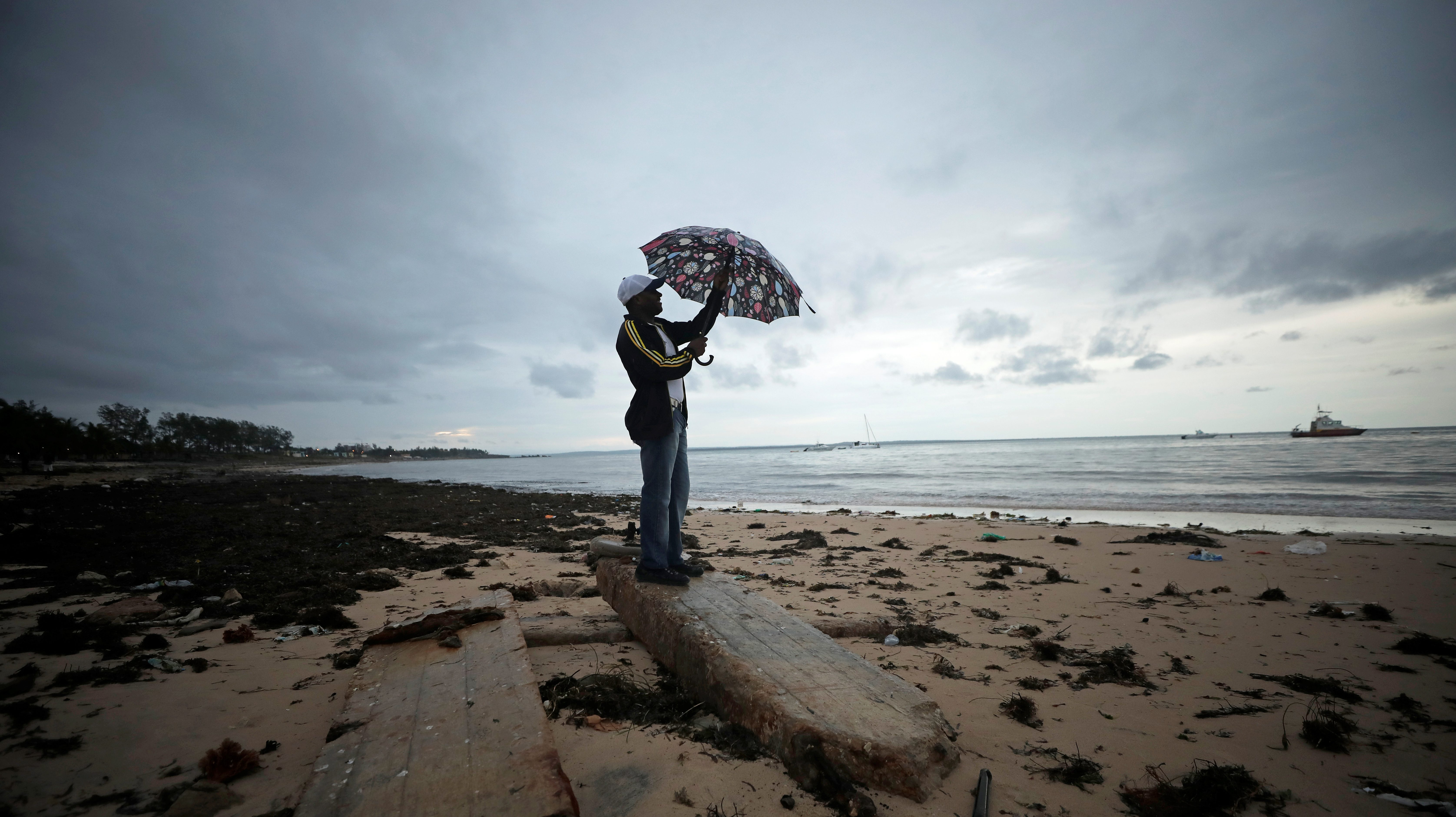 A man holds an umbrella beneath storm clouds over Wimbe beach, as the region braces for further rainfall in the aftermath of Cyclone Kenneth in Pemba Mozambique