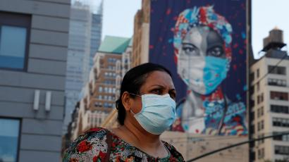 A woman wearing a mask stands in front of a New York building with a mural of a healthcare worker on it.