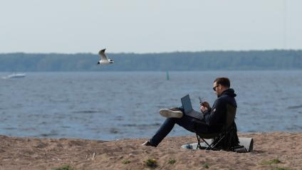 A man uses his smartphone and laptop as he sits on the shore of the Gulf of Finland.