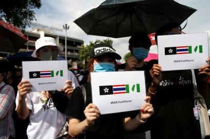 Pro-democracy protesters in Bangkok hold up a Milk Tea Alliance posters
