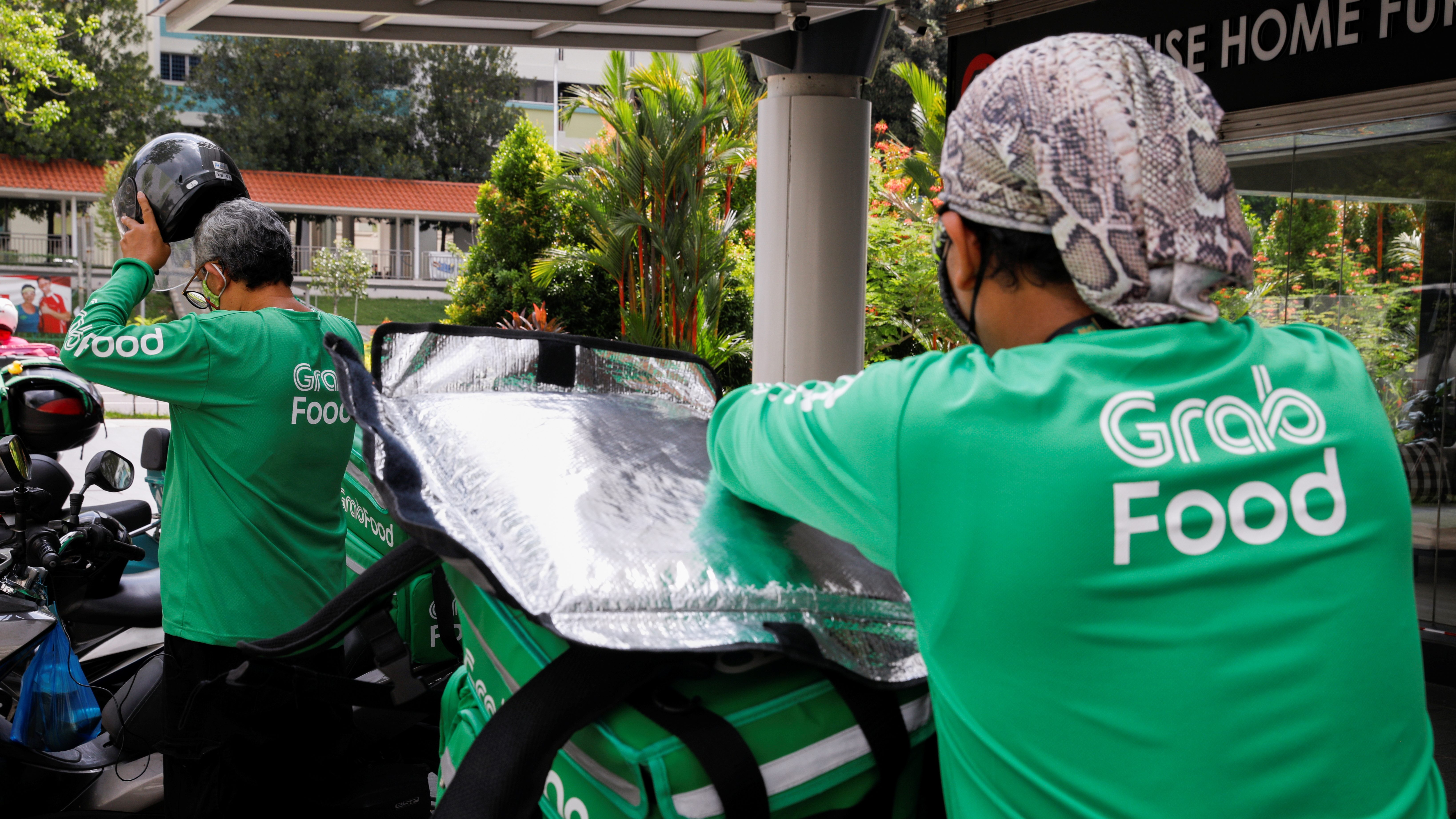 Food delivery riders get ready for a delivery outside a shopping mall, amid the coronavirus disease (COVID-19) outbreak in Singapore, May 26, 2020.