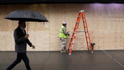 Workers use sheets of plywood to cover the windows of Macy's department store