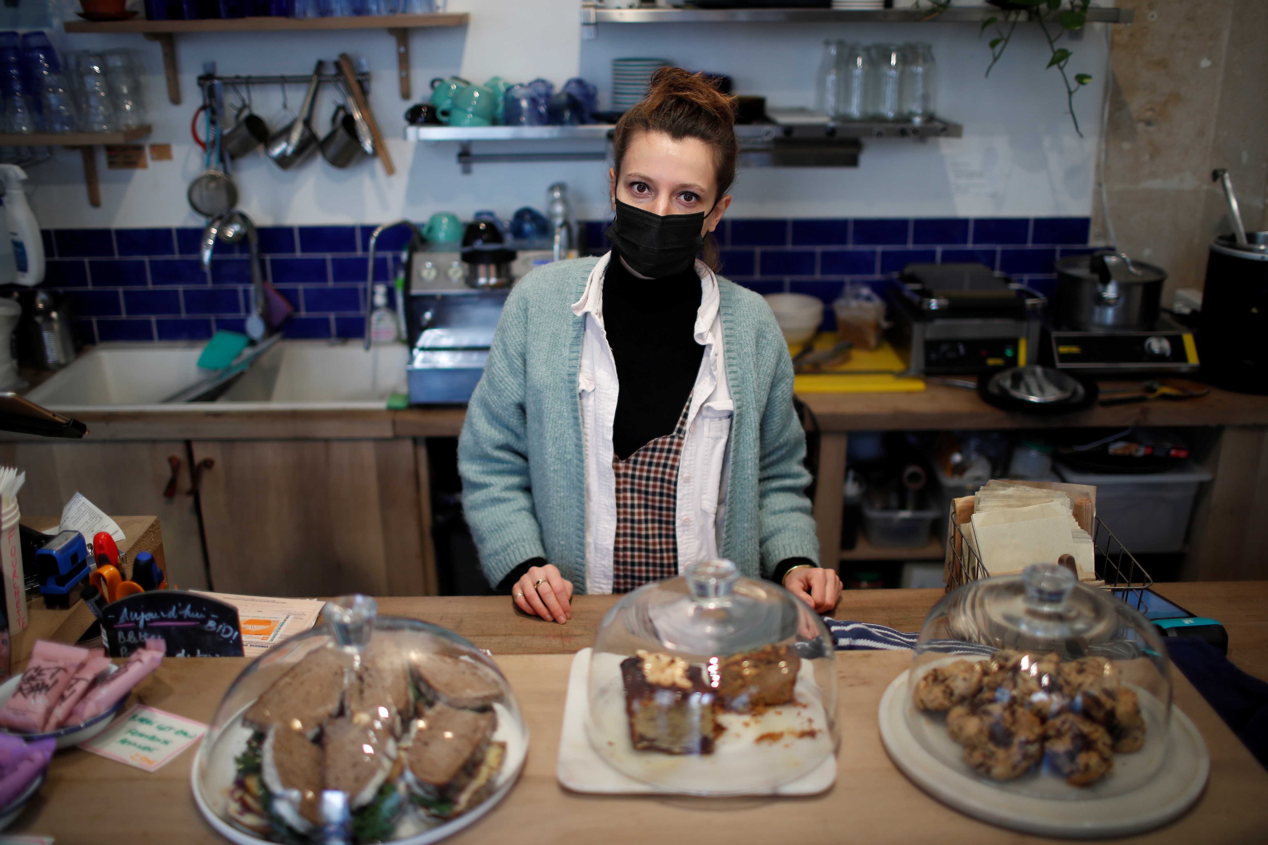 A woman wearing a mask behind baked goods at a coffeeshop or bakery