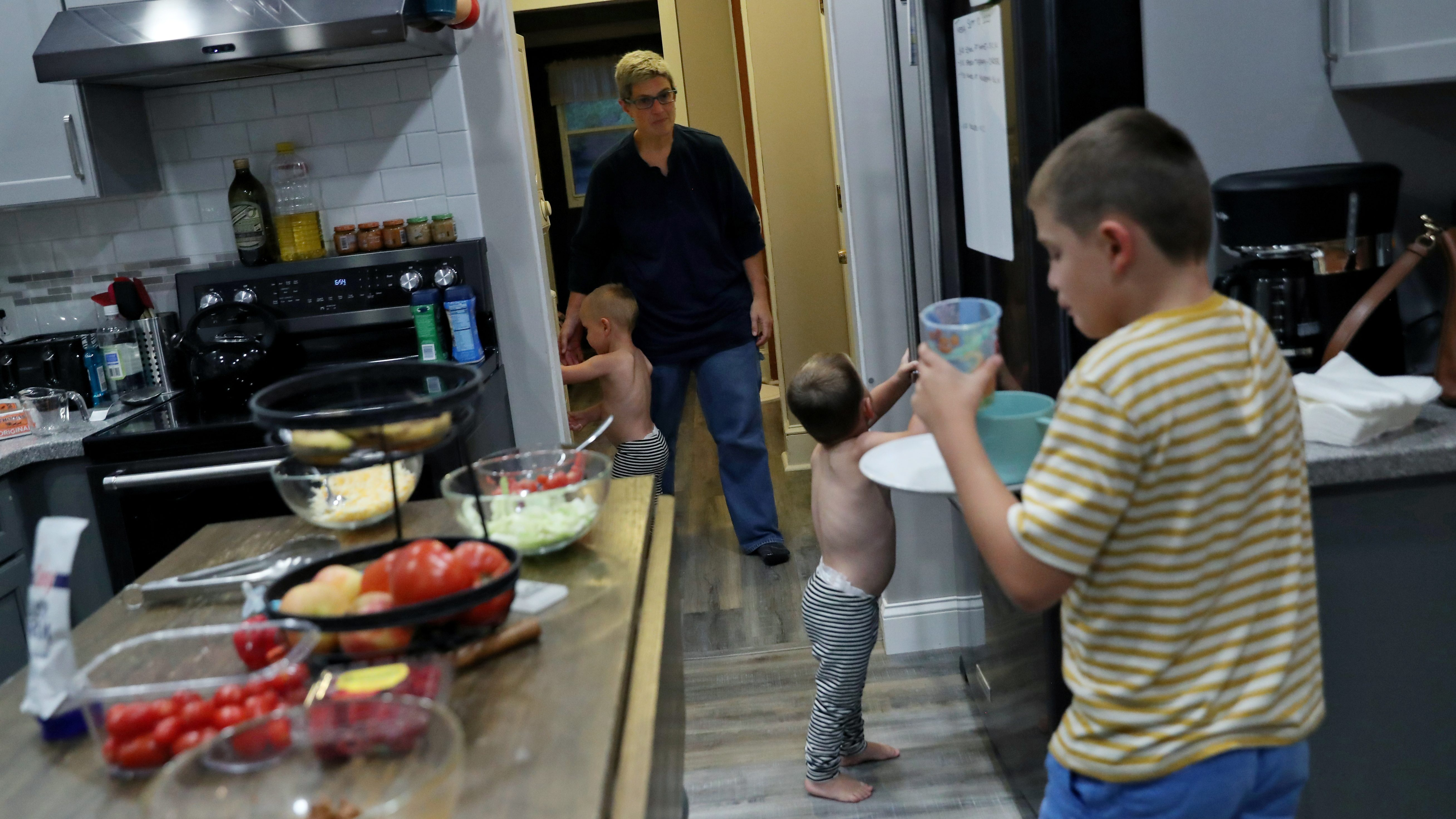 Rachel Newman herds her twin boys as her oldest, Benny, 9, brings his dinner dishes into the kitchen at the Newman home in Pitman, New Jersey, U.S., September 10, 2020.