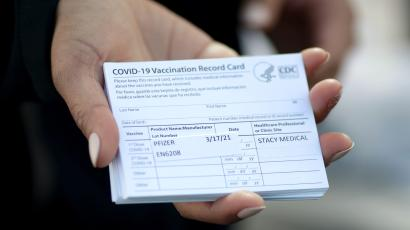 A medical worker holds Pfizer coronavirus disease (COVID-19) vaccination cards at a mobile vaccination drive for essential food processing workers at Rose & Shore, Inc., in Vernon, Los Angeles