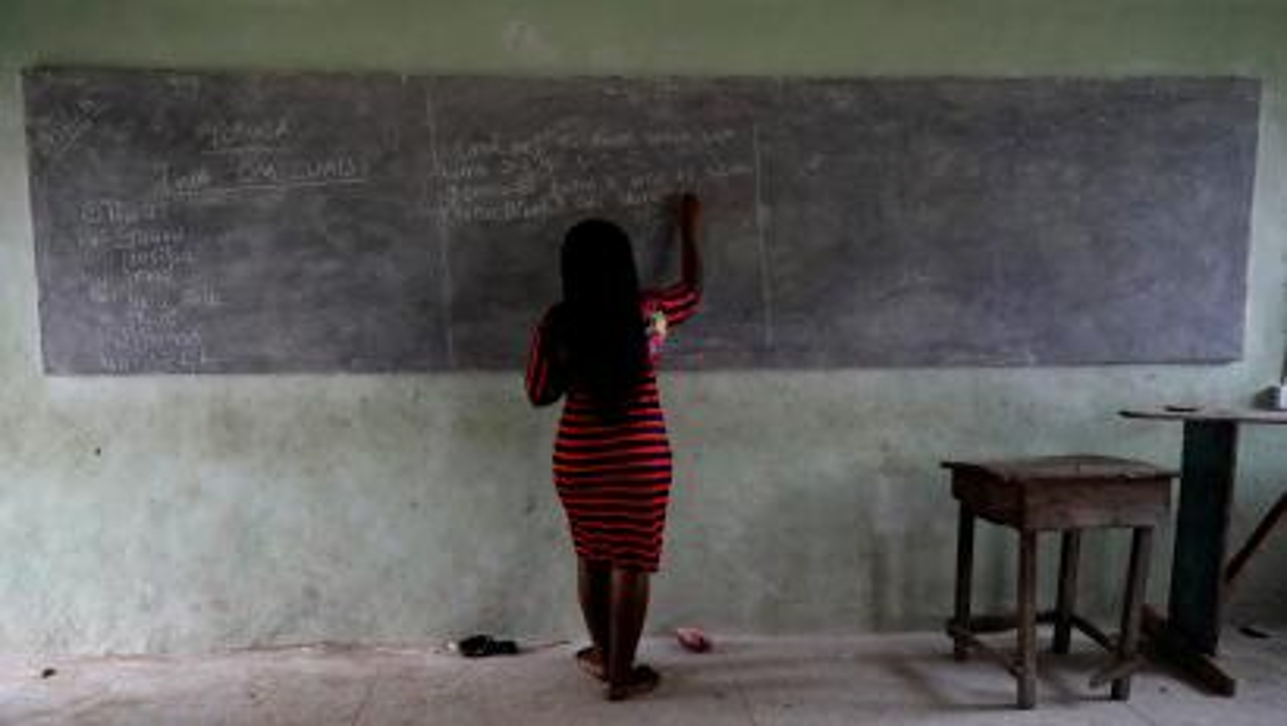 A teacher writes on a chalk board as she teaches a class at Ilorin Grammar School, in Ilorin, Kwara state, March 24, 2021.