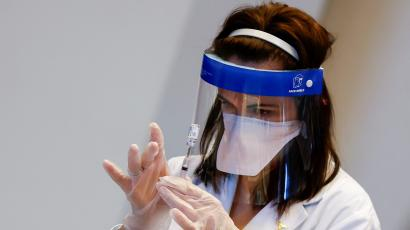 A person wearing a face mask and a face shield holds up a syringe of the Johnson and Johnson Covid-19 vaccine.