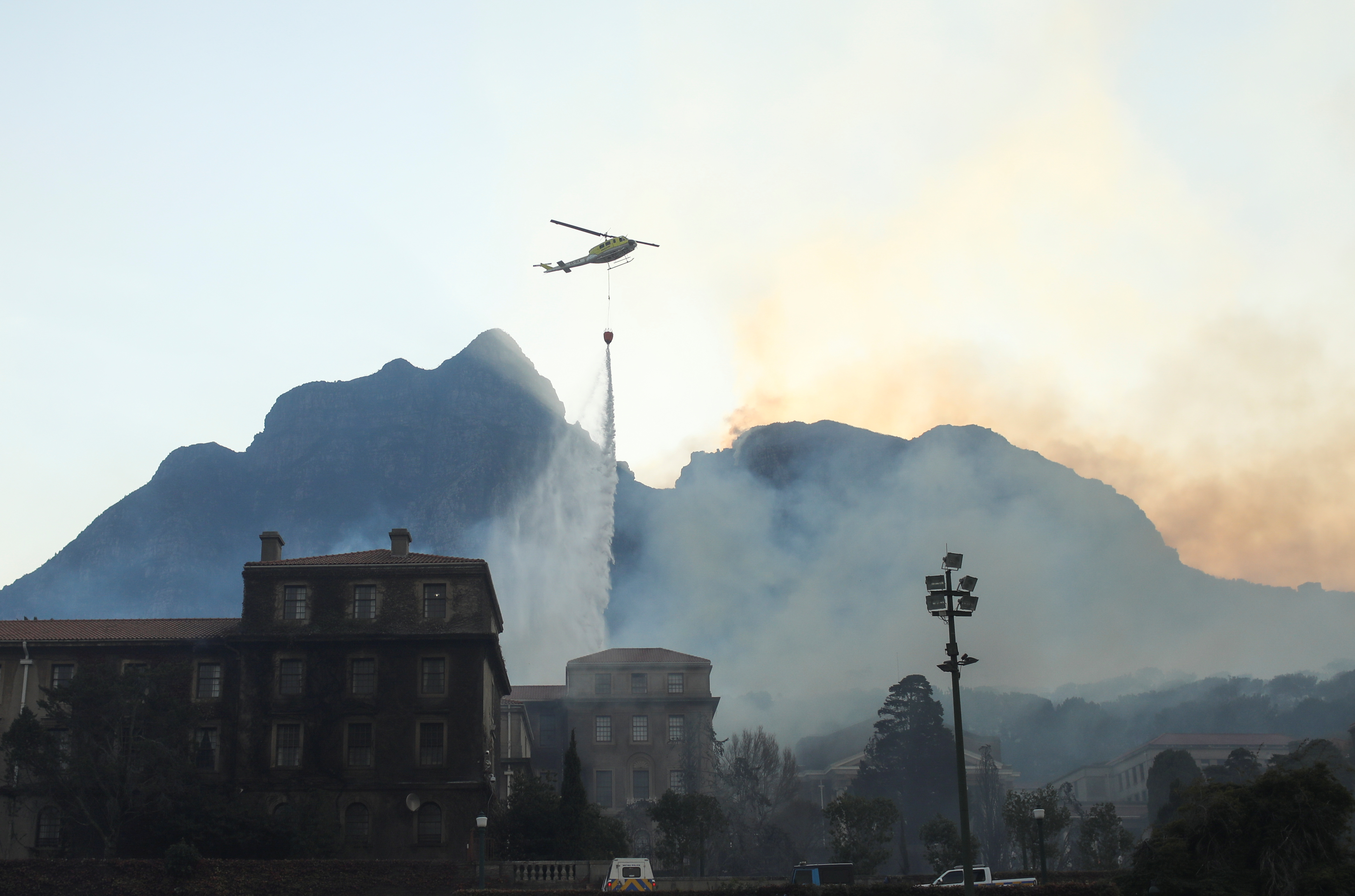 A helicopter drops water as the library at the University of Cape Town burns after a bushfire broke out on the slopes of Table Mountain in Cape Town on April 18.