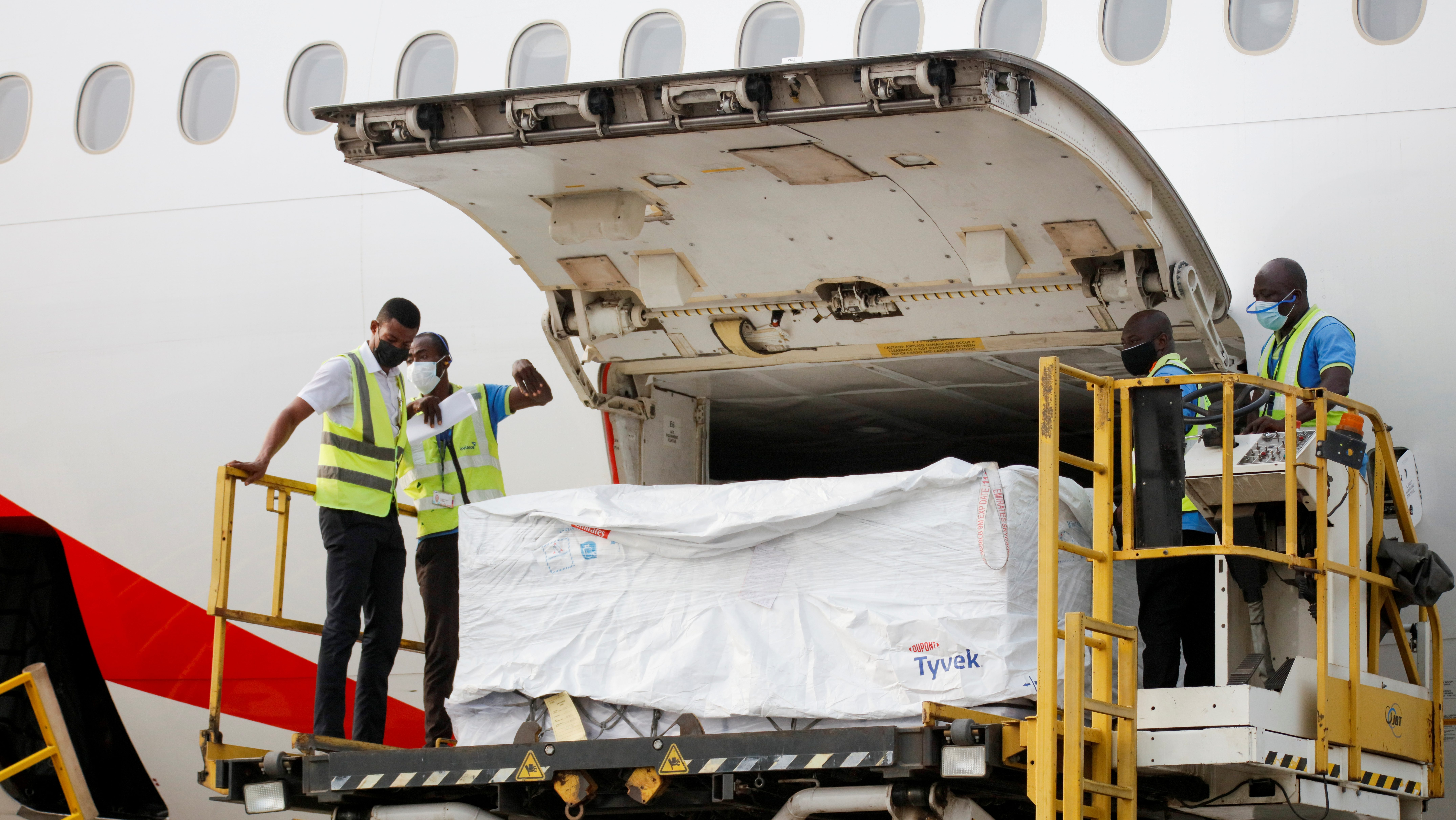 Workers offload AstraZeneca/Oxford vaccines as Ghana receives its first batch of Covid-19 vaccines under the Covax scheme on Fe. 24.