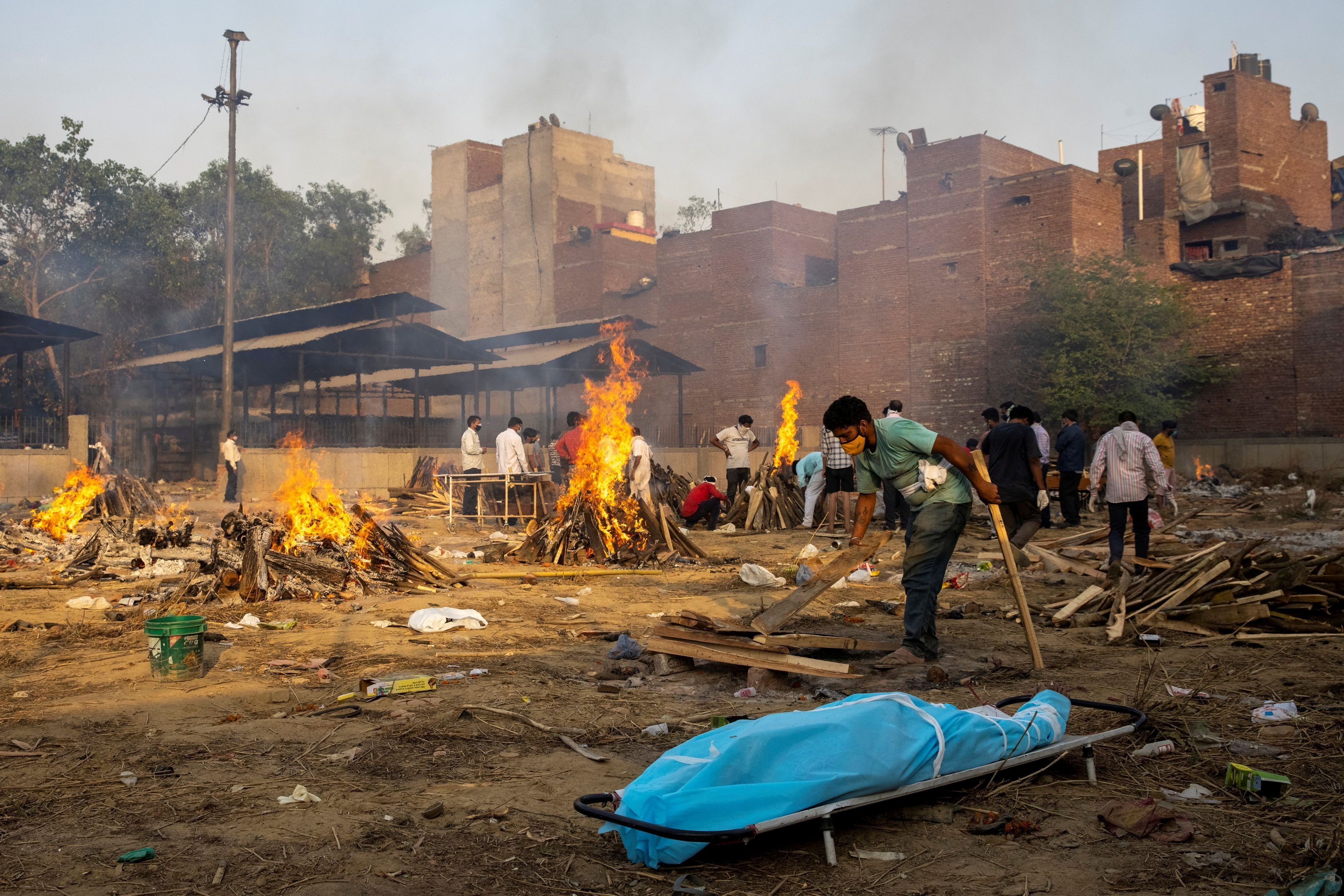 A man prepares a funeral pyre to cremate the body of a person, who died due to the coronavirus disease (COVID-19), at a crematorium ground in New Delhi