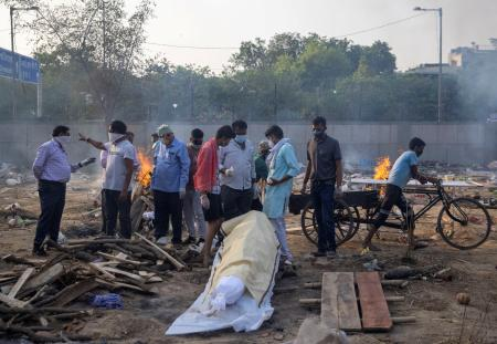 Relatives prepare to cremate the body of a person, who died due to the coronavirus disease (COVID-19), at a crematorium ground in New Delhi