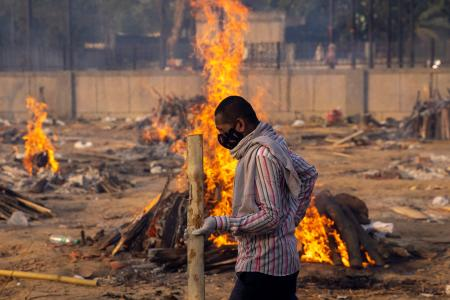 A man walks past burning funeral pyres of people, who died due to the coronavirus disease (COVID-19), at a crematorium ground in New Delhi