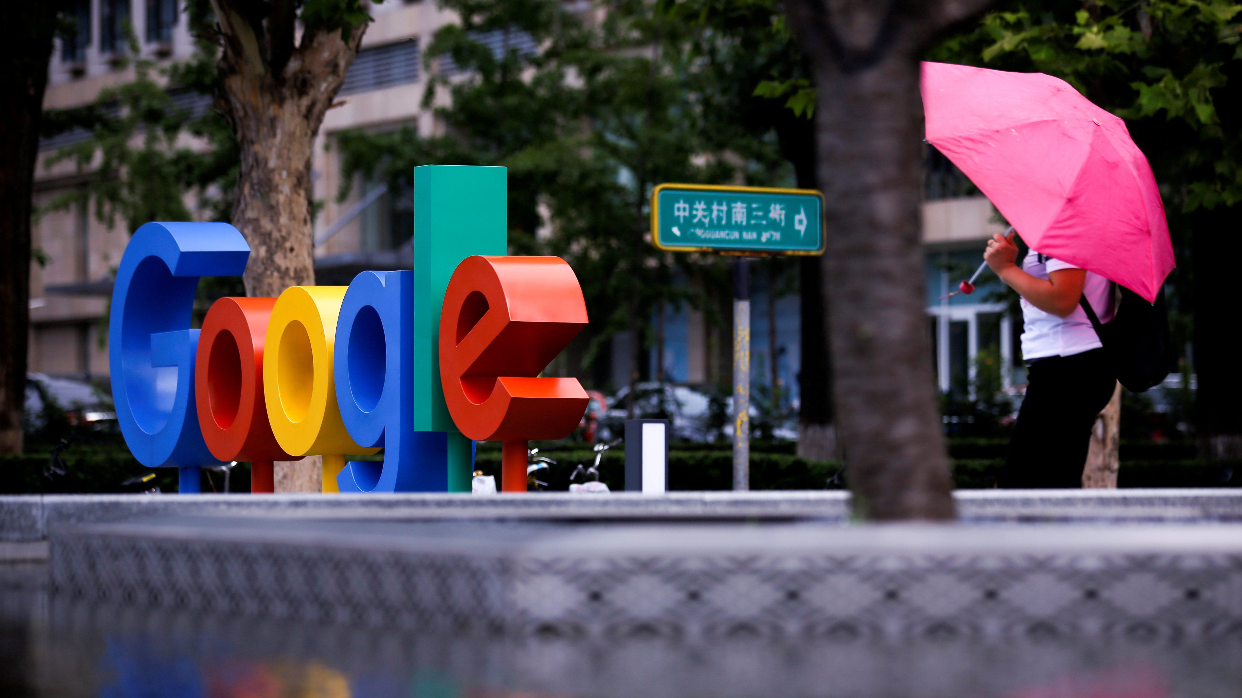 Google's logo is seen on a rainy city street.