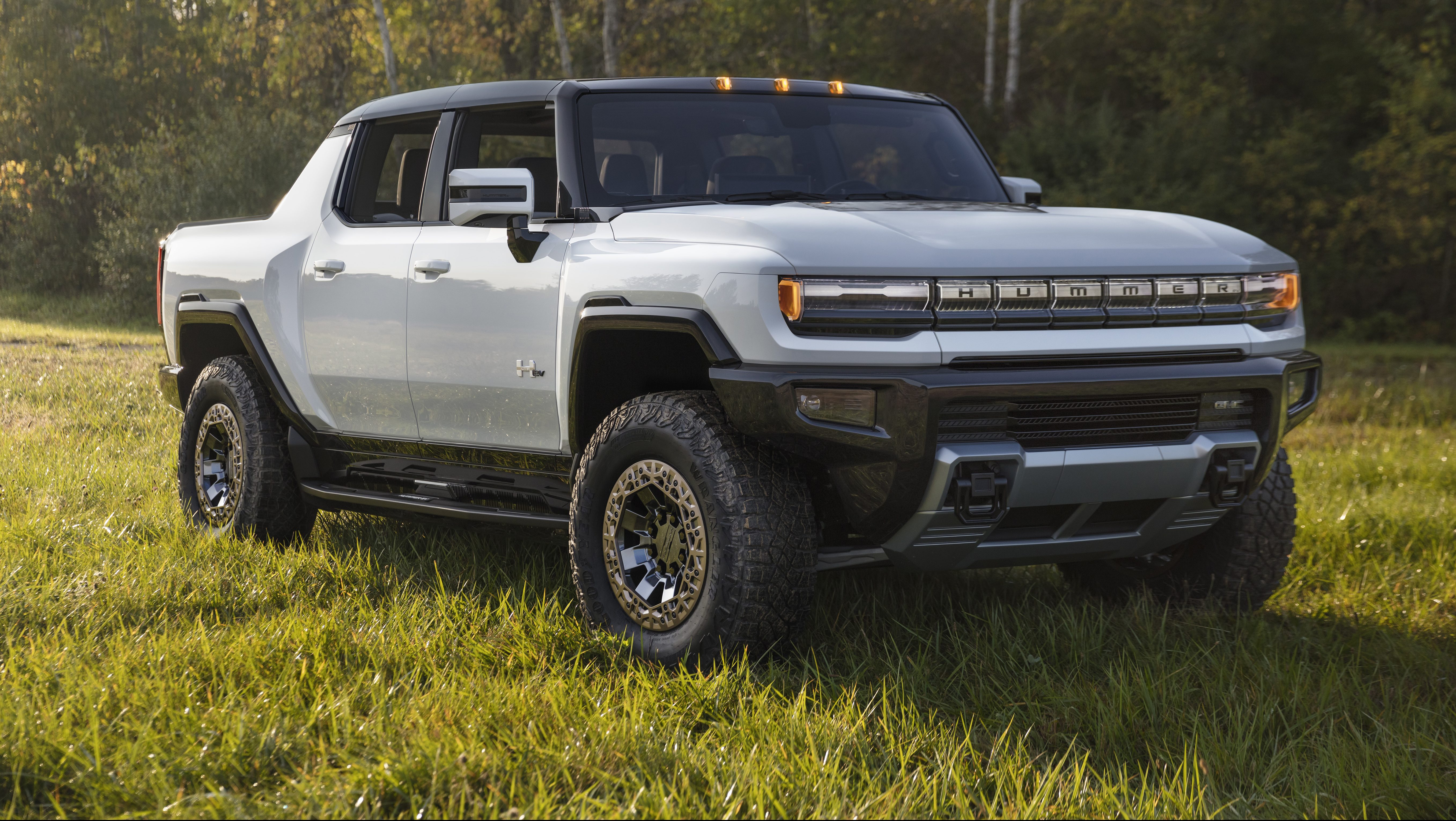 A photograph of a silver 2022 GMC Hummer EV parked in a field of grass.