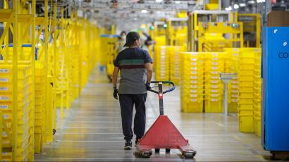 An Amazon worker pulls a cart in a warehouse, passing yellow bins