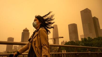 A woman wears a protective mask as she walks in heavy winds during a seasonal sandstorm on April 15, 2021 in Beijing, China.