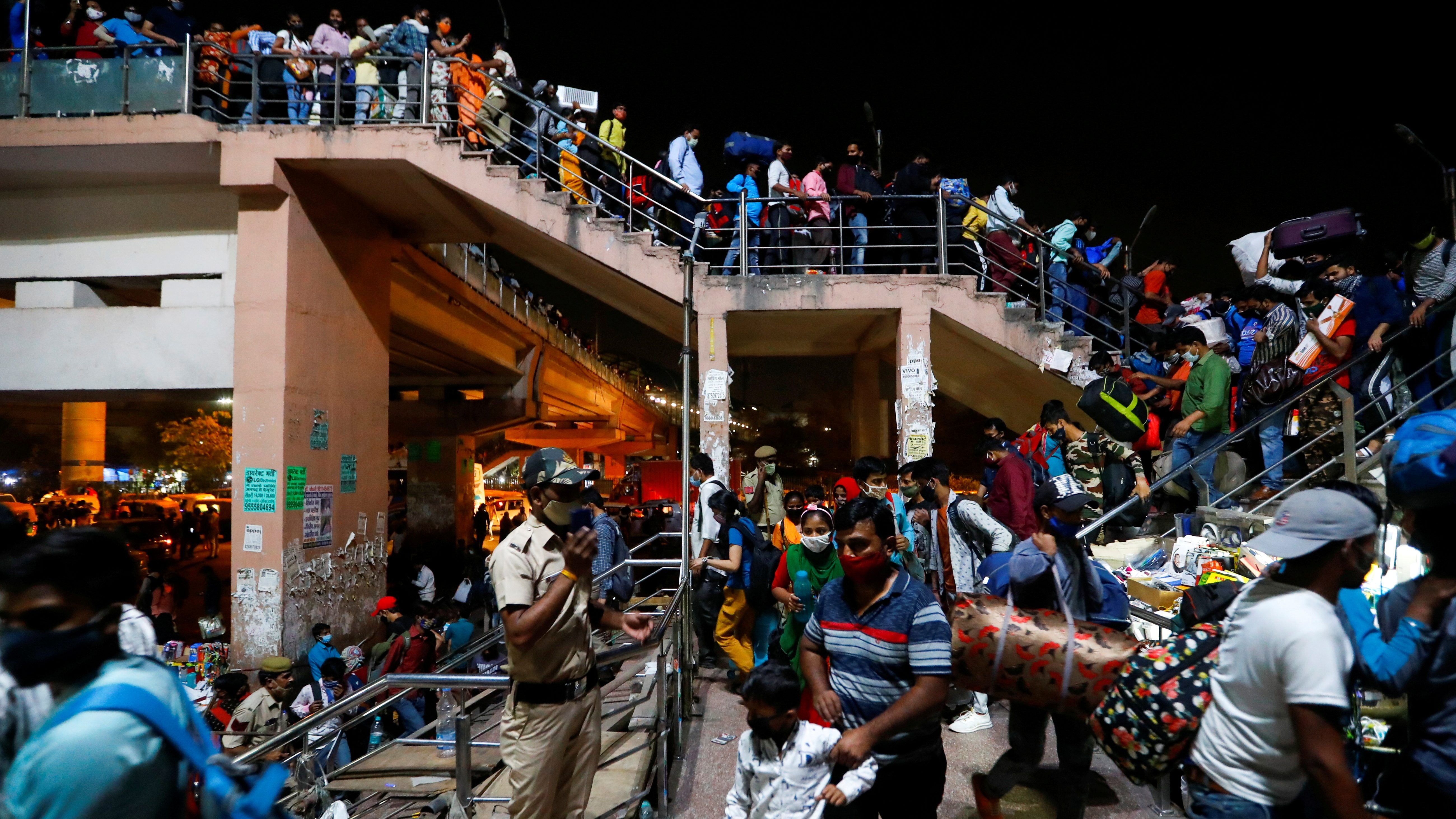 Migrant workers arrive at a bus station to board buses to return to their villages after the Delhi government ordered a six-day lockdown
