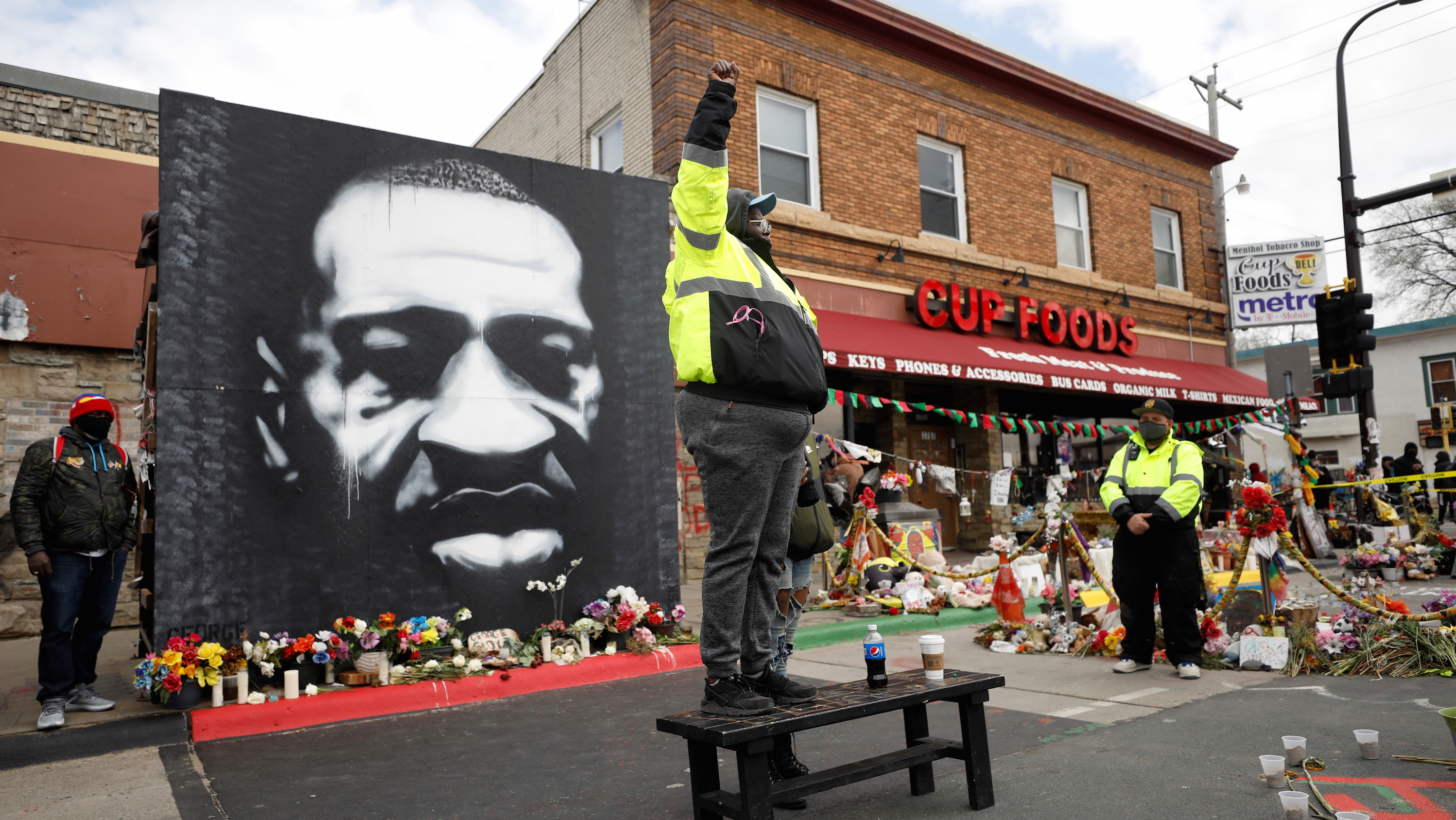 A mural of George Floyd by the Cup Foods store where he was murdered, with a man standing with a raised fist in the foreground
