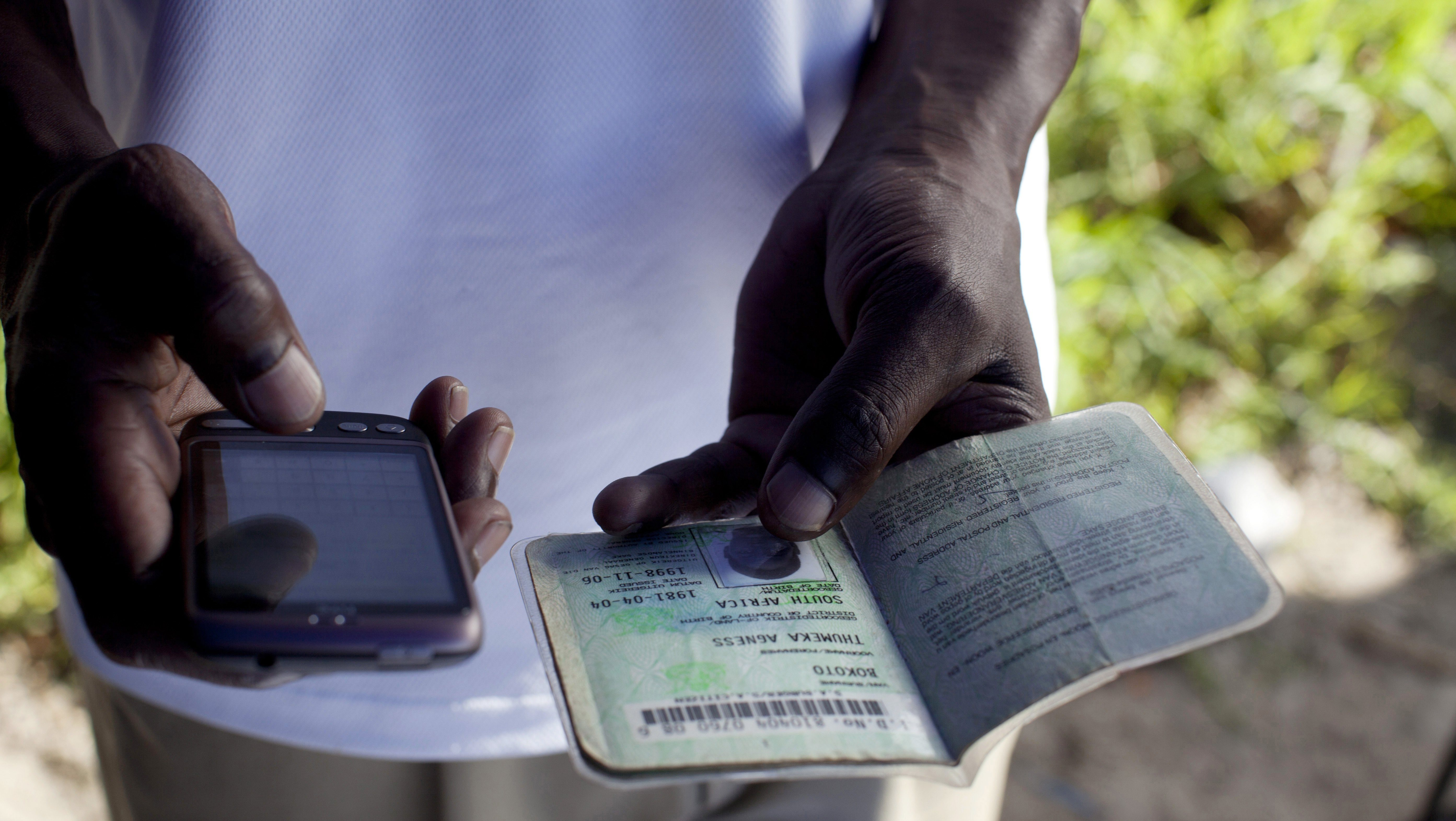 An employee of a bank checks a South African ID document via mobile phone as he sells accounts on the street in 2011 in Khayelitsha, the poorest and largest township outside Cape Town, South Africa.
