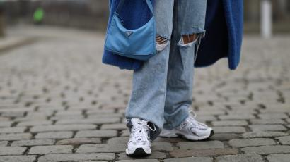 A woman carries a baby blue Prada bag and wears a blue Max Mara coat, baggy Zara jeans, and New Balance sneakers