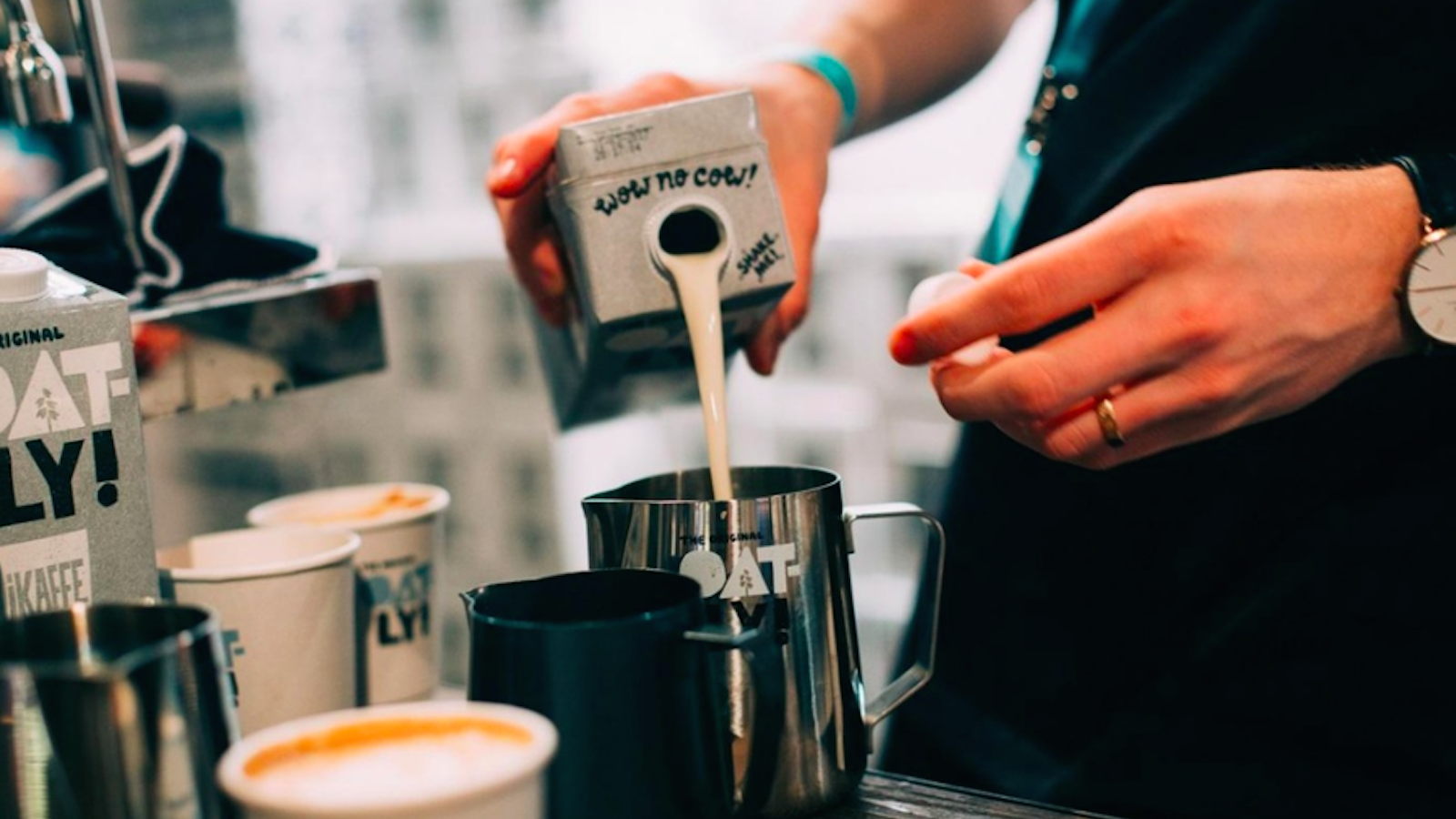 a barista's hands pouring oatly into a latte