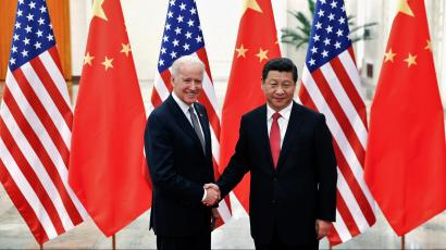 Xi and Biden shake hands in front of a row of American and Chinese flags