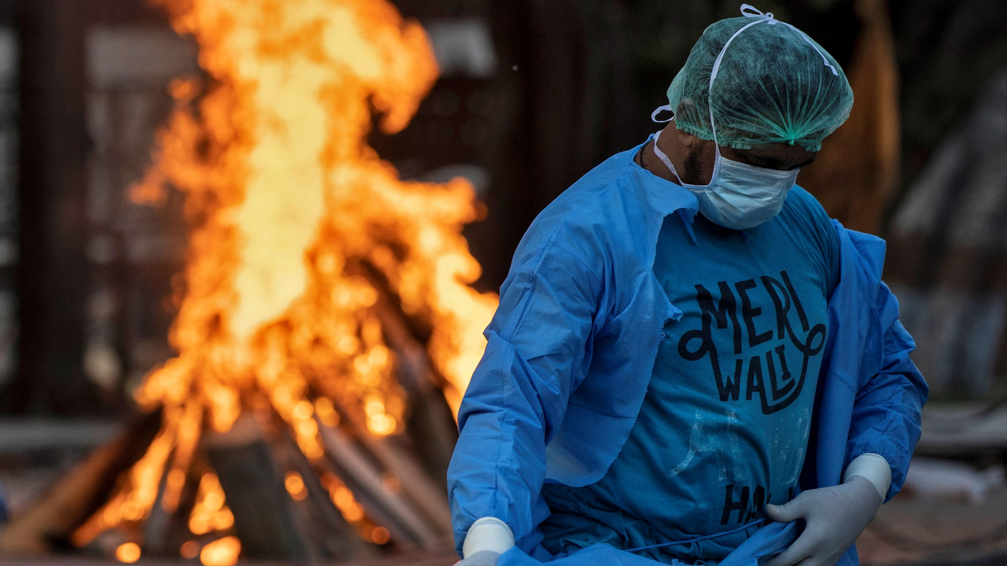 Mohammad Aamir Khan, an ambulance driver, changes his personal protective equipment (PPE) as a woman who died due to the coronavirus disease (COVID-19), is cremated at a crematorium in New Delhi