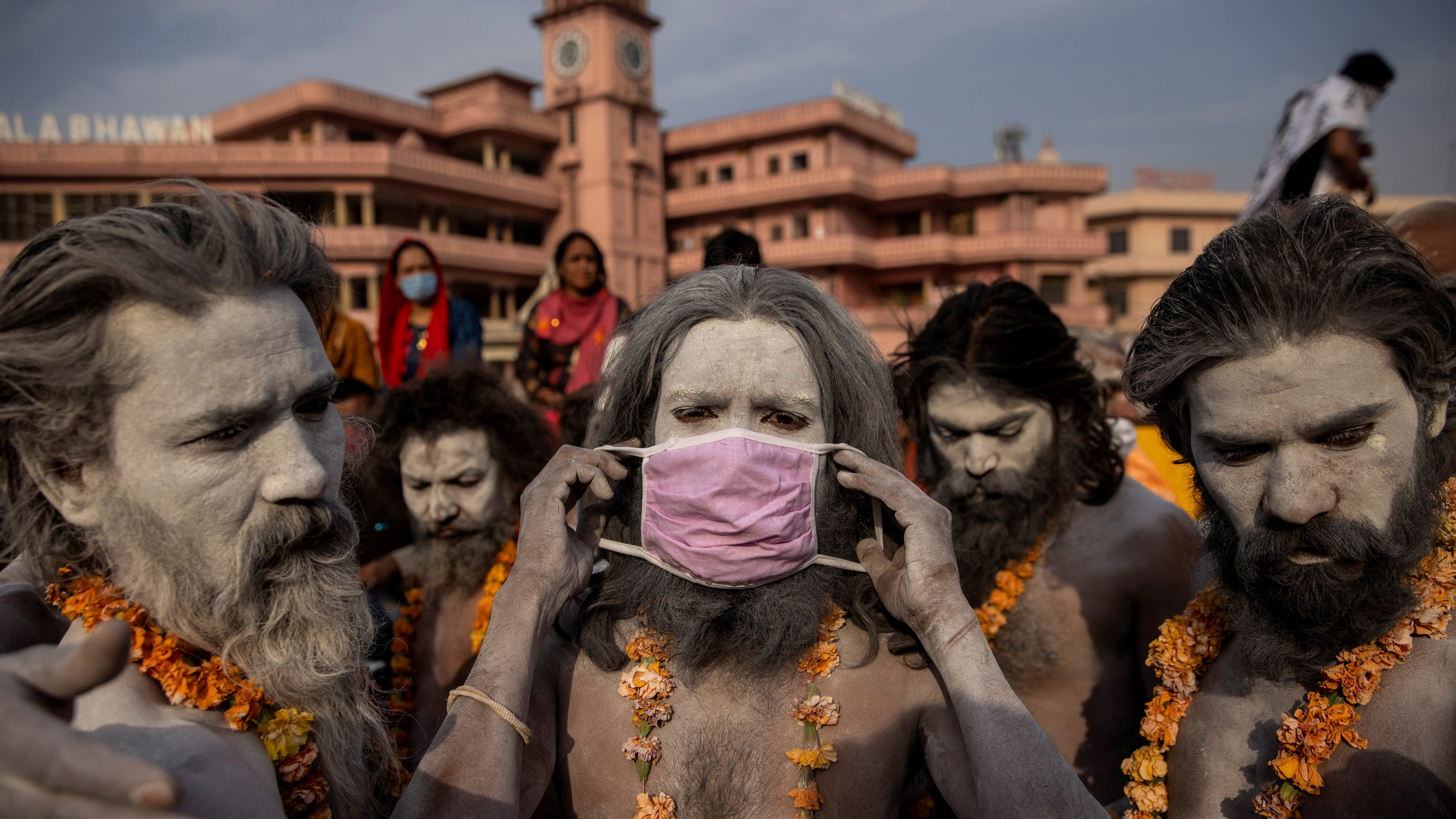 """A Naga Sadhu, or Hindu holy man wears a mask before the procession for taking a dip in the Ganges river during Shahi Snan at """"Kumbh Mela"""", or the Pitcher Festival, amidst the spread of the coronavirus disease (COVID-19), in Haridwar"""