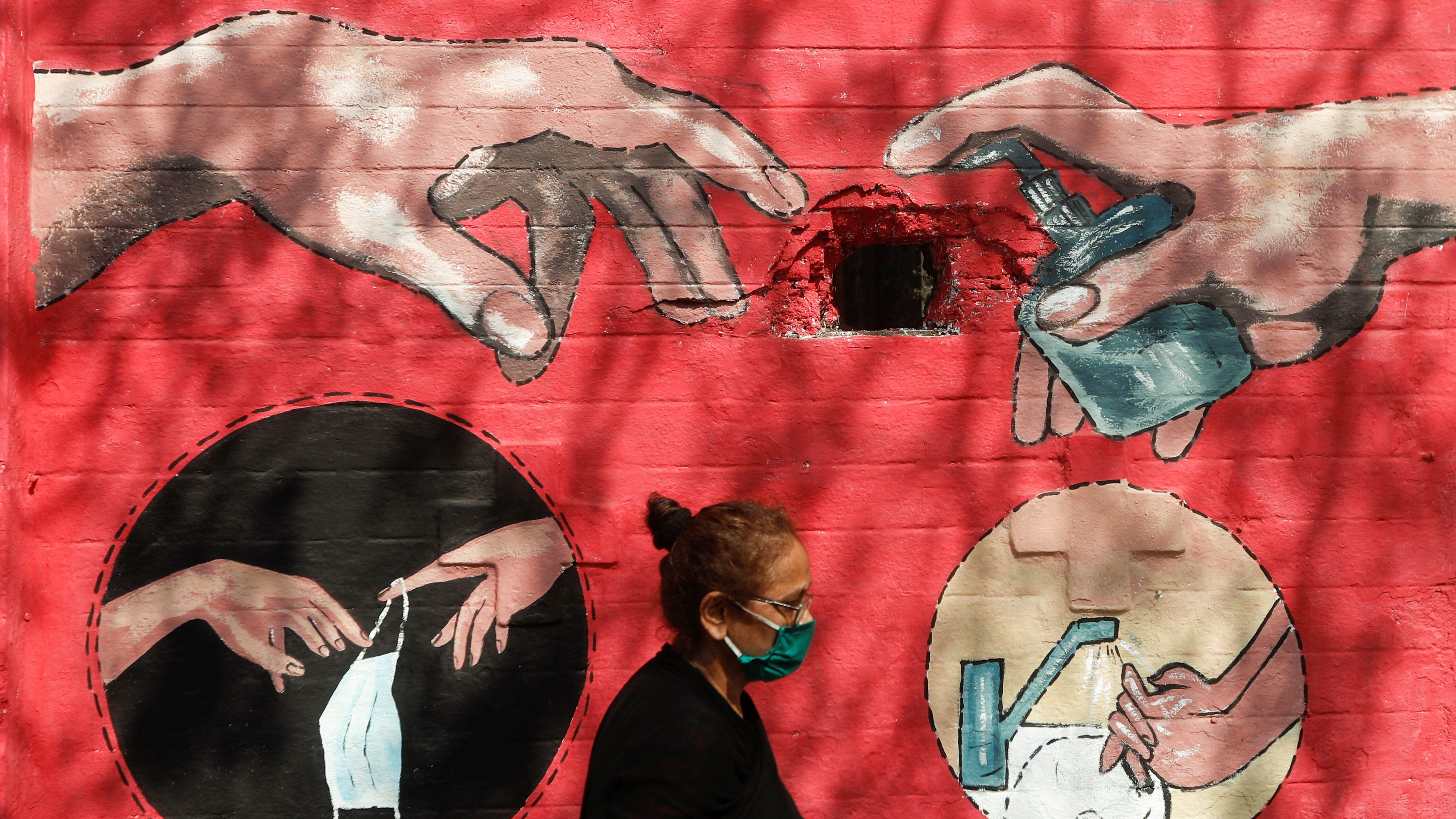A woman walks past a graffiti, on a street, amidst the spread of the coronavirus disease (COVID-19) in Mumbai