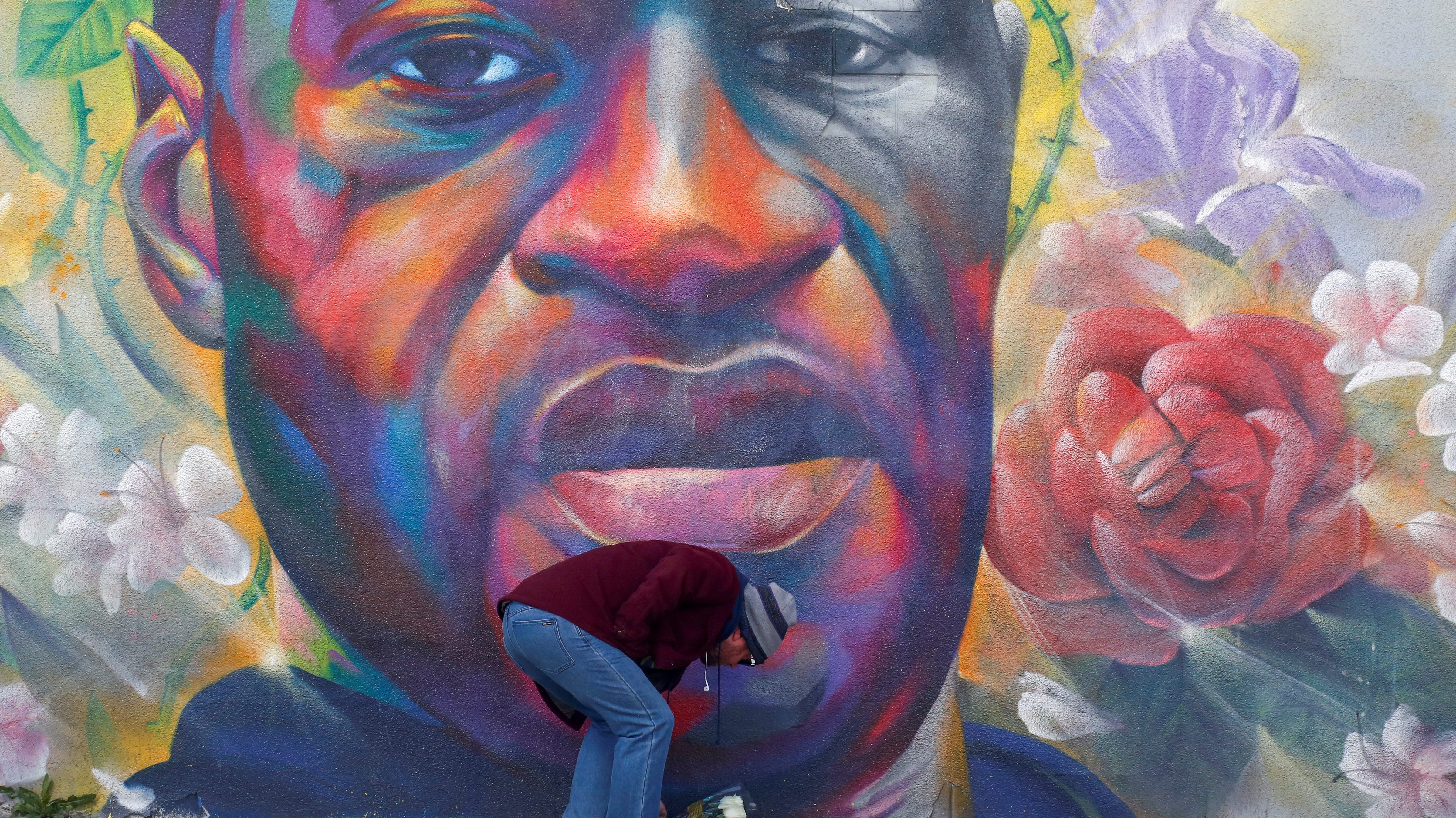 A man places flowers at a mural of George Floyd after the verdict in the trial of former Minneapolis police officer Derek Chauvin, found guilty of the death of Floyd, in Denver, Colorado, U.S., April 20, 2021.