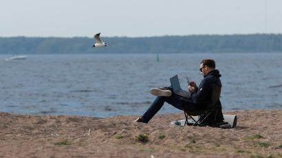 man working with laptop on a beach