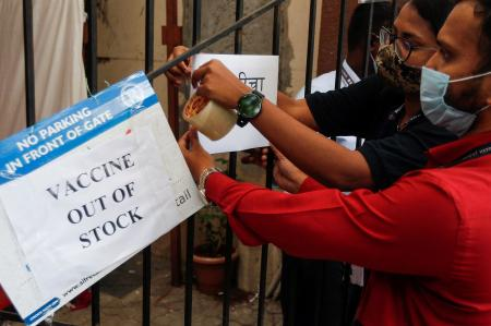 FILE PHOTO: Health workers attach a notice on the shortage of COVID-19 vaccine supplies at a vaccination centre in Mumbai