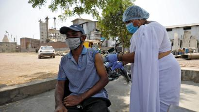 A rice mill worker receives a dose of COVISHIELD, a coronavirus disease (COVID-19) vaccine manufactured by Serum Institute of India, during a COVID-19 vaccination drive at Bavla village
