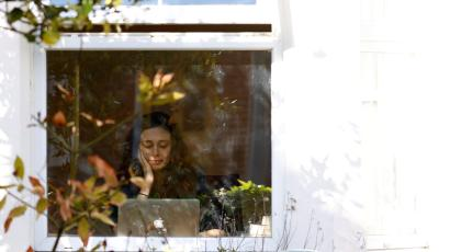 a woman sitting at her laptop, glimpsed through the window of her home