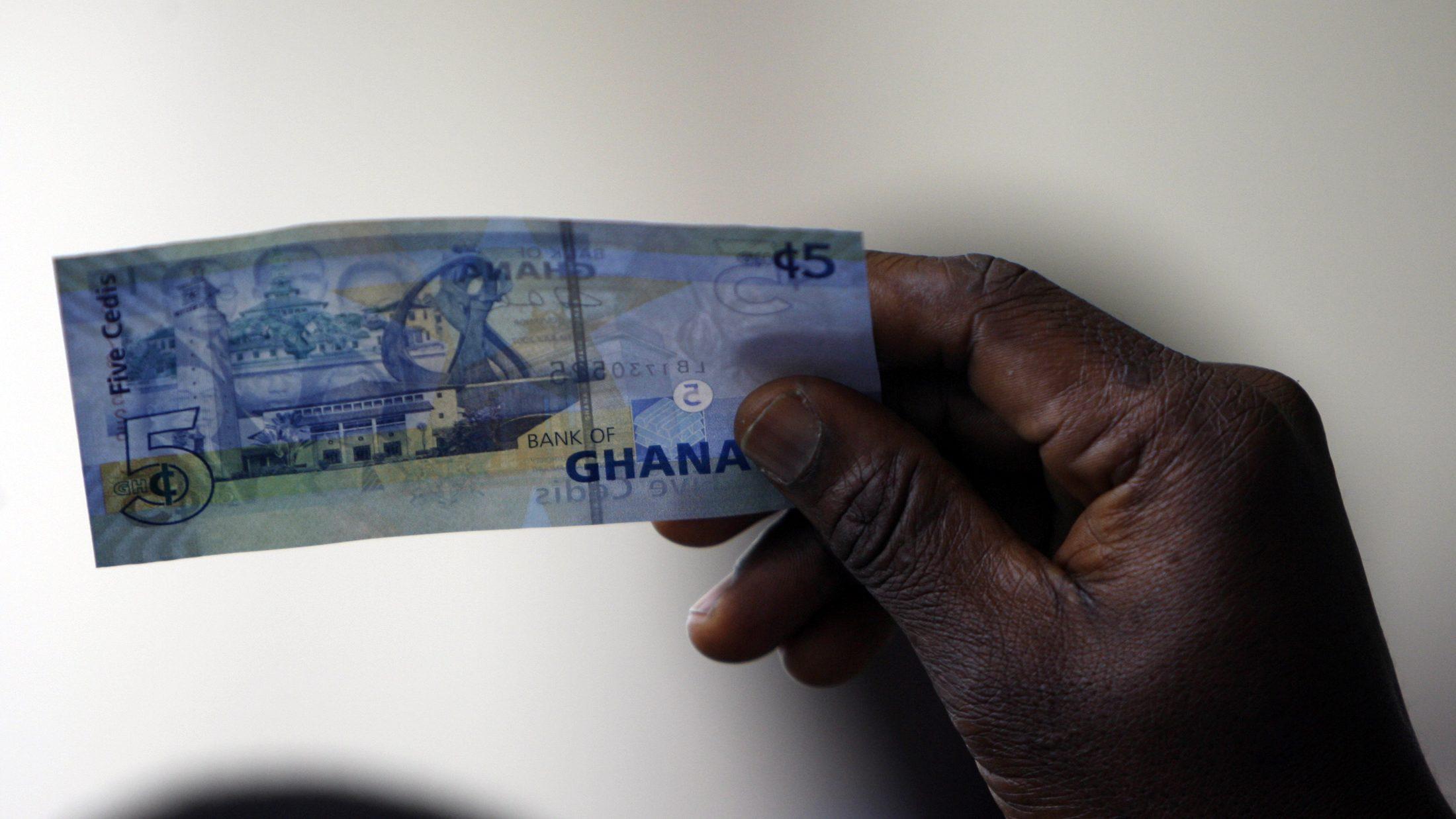 A man holds a Ghanaian five cedi note.