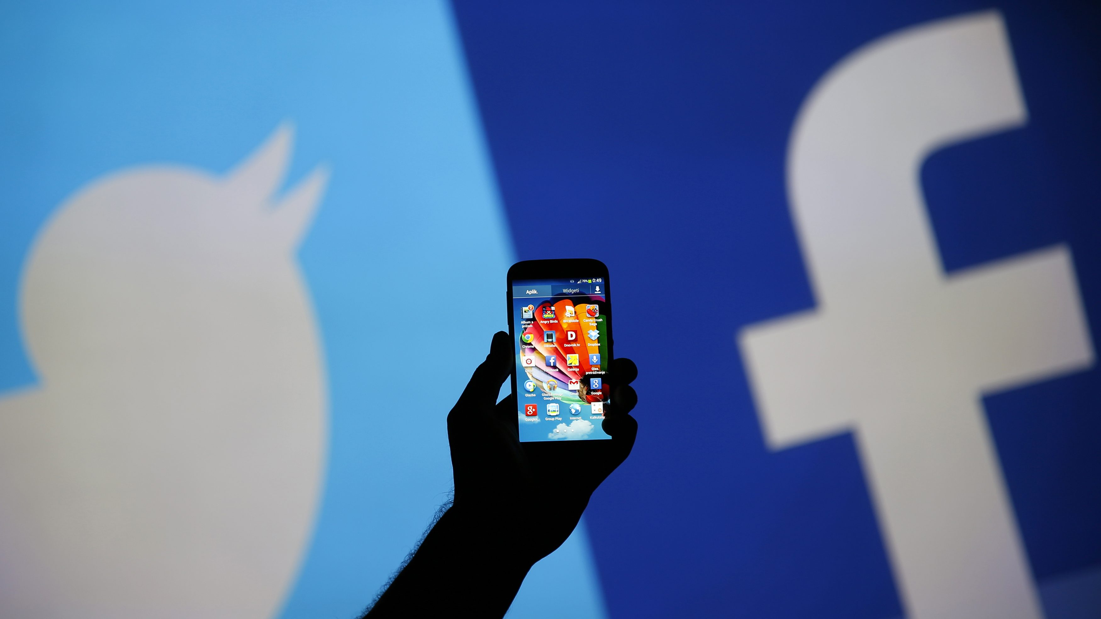 A man holds up a Samsung S4 smartphone against a video screen with Twitter and Facebook logos in this photo illustration taken in the central Bosnian town of Zenica