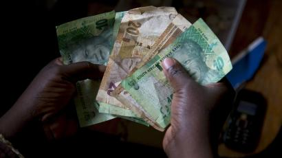 A shopkeeper counts out change above her cash box at her shop in Durban, South Africa.