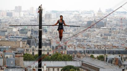 Tightrope walker Tatiana-Mosio Bongonga advances on a tightrope as she scales the Monmartre hill towards the Sacre Coeur Basilica (not pictured) in Paris, France, July 20, 2018.